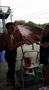 The Purple Painted Lady Patio Umbrella Primer Red In Process on loading dock